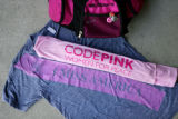 Buttons decorate Alicia Forrest's pink backpack beside her CodePink scarf and a t-shirt that reads...