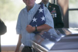 0466  A man carries the flag that was draped on Staff Sgt. Wesley Hunter's casket during a burial...