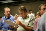 Jeff Stamper (cq) (middle) looks at RTD statistics with Blaine Nickeson (cq) during an RTD meeting...