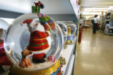 DM0973  Tuesday_Morning_Holiday_Merchandise+55072 A Santa Claus snow globe sits on the shelf as a...