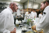 Chef/instructor Michael Scott, left, coaches culinary student Steve Youngman, who's making...