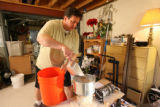 David Anderson mills the barley for his cream ale beer in a home-made mill in his basement.  He...