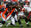 0016 Denver Broncos' (32) Dre Bly, and (58) Nate Webster wrap up Tampa Bay Buccaneers (34)Earnest...