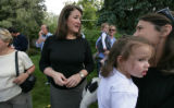 Dianna DeGette talks with supporters like Yvette Frampton holding daughter Kirkel at a backyard...