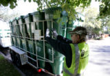 A Denver Solid Waste Recycling employee ( refused to give his name) unloads 65 gallon green carts...
