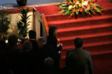 (PG10569) John Dempsey's widow, Pam, holds the state flag at the end of the funeral. The service...
