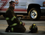 (Cheyenne, WYO. - 12 28, 2004) -- A weary-looking firefighter kneels on 16th Street in downtown...
