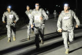 Soldiers race to the finish line in the three mile buddy run in phase one of their PT test in the...