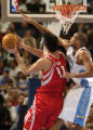 (Denver, CO., January 9, 2004) Marcus Camby defends against Yao Ming in the first half of the...