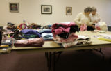 Ruth Klein (cq), left,  peeks into a package of hats she knitted with fellow volunteer Nancy...