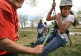 MJM068  Volunteer, Bernie Holien (cq), left, helps Laura Espino (cq), 13, ride a zip line as she...