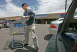 BG0076 Lei Zhu, CQ, loads a 20lb bag of Kokuho Rose rice into his car which has recently risen in...