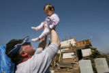 MJM556  Chuck Gully (cq) holds up his youngest daughter, Erika Gully, 11 months, outside their...