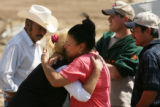 MJM303 Ilde Dominguez (cq), left center, is hugged by family members outside the remains of her...