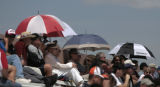 Fans use umbrellas to protect themselves from the sun, Friday morning, May 9, 2008, at Denver All...