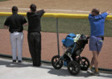 Dan Pfannenstiel (cq) brought his 8 month old son, Fin, to 5a baseball, Friday morning, May 9,...