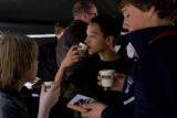 13 year old Brandon Medina surrounded by friends sips some Tazo tea while in the backgrouns Chef...