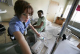 (083) Kalina Miller, a nursing student, adjusts the oxygen level for one of her patients, Gerald E...