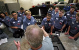 (080) Pickens Technical College Auto Mechanics teacher Ed Wilson, center, explains the day's...