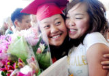 Arvada graduate Kayoua Cha receives a bouquet of flowers and hug from longtime friend Katy Thao...