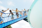 Reuben Fernandez, 14, left, of Montbello, reaches for a high-five as he climbs the slide steps at...