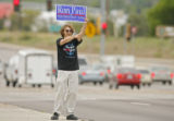 DM0128  T.C. Bell, 21, of Denver holds a Ron Paul sign and protests Sen. John McCain along Havana...