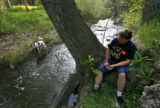 DM0191  Terry Smith takes his son's dog Dobie for a walk along Bear Creek just blocks away from...