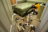 MJM172  Kenny Coffman (cq) throws away damaged items from his and his roommate's home Saturday...