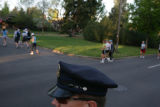 Denver Police Officer Matt Ruckle (cq) patrols runners at the corner of 17th Ave. and Albion...
