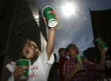 DM1055  Sarah Gardner, 8, left, and Greg Sauer, 6, hand out water to thirsty runners at the top of...