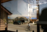 MJM498  A bicyclist is reflected along with Cornerstone Dr. in the window of the tornado damaged...
