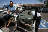 (PG2137)  Gautier Pe?a (left) replaces a windshield with help from Angel Leon (center) and Uriel...