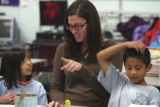 Third grade teacher Siri Lewis (cq) helps students Jessica Padilla (cq), left, and Pedro...