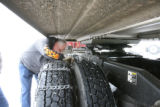 Ron Wand (cq), Tomahawk Transport, Inc. works on putting on snow changes to go over Loveland Pass,...