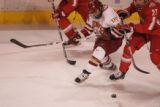 #14 Jesse Martin (cq) of Denver fights with #27 Mike Folkes (cq) of Ohio St., for the puck as the...