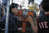 (from left)  6 year-olds Daniel Avila (cq), Johnny Lee's grandson, peeks through the fence at...