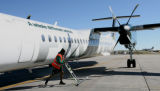 Doc Harris (cq) moves a dolly, after getting a Frontier Bombardier Q400 Turboprop plane ready for...