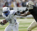 NYMG103 - Air Force running back Asher Clark (17) holds off Army defender Donovan Travis during...