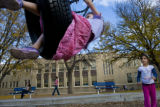 Mia Kieling, 6, (cq) swings after Ella Cutrona, 7, (cq) pushes her as they play at Amos Steck...