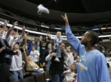 (Denver, CO  on 12/29/2004 ) - Denver Nuggets center Marcus Camby, right, tosses one of his shoes...
