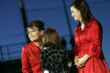 Gov. Sarah Palin listens to her daughter Piper, while her other daughter Willow watches as she...
