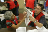 Election workers Anne Deaderick (cq) left, and Sean Essex look at a ballot that the ballot scanner...