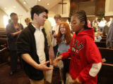 P.J. Allen, right, shakes hands with Christopher Nguyen, left, as Rebecca Denny looks on at the...
