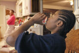 P.J. Allen looks to his grandmother, Deloris Watson, while finishing a breakfast drink early in...