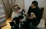 David and John (l-r) hold onto their 4 dogs in their living room. Two interior designers John...