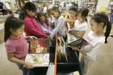 Third graders from McGlone Elemetary School at 4500 Crown Blvd. in Denver pick out books from a...