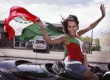 A young woman (UNK) cruiser waving a Mexican flag  embodies the joyful spirit of crusing on...