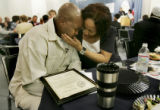 Dolores Clark (cq), rt, comforts her son, Akio Clark (cq), 29, who is emotional after receiving a...