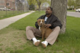 Kerry Price and Honey, his one year old pit bull,  sit together near his home in Denver, Colo....