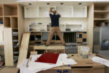 HGTV Dream House project.   Christopher Herr installs red doors on kitchen cabinets that he...